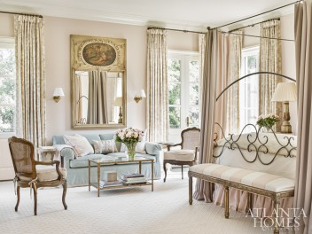 Accented with draperies and luxurious bedding, the light-filled master bedroom boasts a seating area with a plush sofa in light blue fabric and antique chairs. The sconces are from Oliver Street Designs.