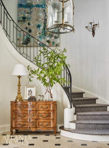 In the front foyer, a custom metal railing by Calhoun Design & Metalworks graces the curvaceous stairway, which features a stylish animal print runner by Stark. The stairwell painting is by Kiki Slaughter.