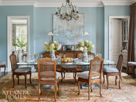 A contemporary work of art by Hutton Snellings coordinates with colors in the Oushak rug in the luxurious formal dining room. The tabletop is styled with Chinese export rose medallion vases and the client's collection of china and silver.