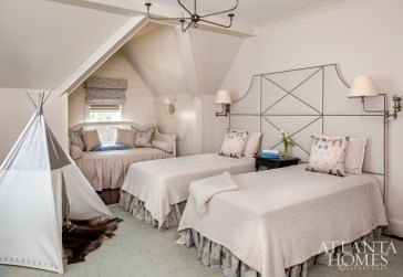 Because the master bedroom is located on the ground floor, the upstairs bedrooms, including this one, are used by both overnight guests and the couple's grandchildren. By using soft, neutral colors and installing one wide upholstered headboard behind the twin beds, Bozeman created a space that caters to both young and old alike.