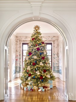 Hardwood floors laid in a herringbone pattern, a scenic wallcovering by Schumacher and a bedecked Christmas tree create a welcoming first impression for holiday guests.