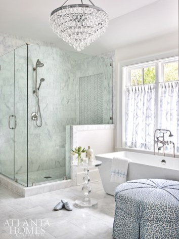 An ottoman from Wesley Hall covered in a blue-and-white leopard print from Cowtan & Tout adds a touch of softness to the master bathroom. The tub is by Victoria & Albert from Ferguson.