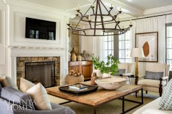 A pair of Visual Comfort iron chandeliers ties together the adjoining living and dining spaces. Pressed foliage by Blackwell Botanicals nod to the home's natural setting.