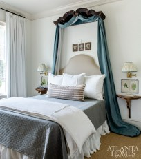 In the guest bedroom, the top of a vintage armoire serves as the bed crown. Other unique accents include framed Italian family crests displayed just above the headboard. To keep things fresh, Schumacher's Deconstructed Stripe wallcovering adds a touch of modern.