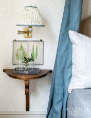 Antique demilune nightstands mounted on the wall add a historic edge to a guest bedroom.