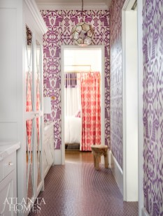 """A Jack-and-Jill bathroom is a purple promised land. In lieu of regular cabinetry, Johnson designed a mirrored cabinet door because, """"two girls sharing the same space requires a lot of mirrors."""" The wallpaper is Quadrille; the lighting is Worlds Away."""