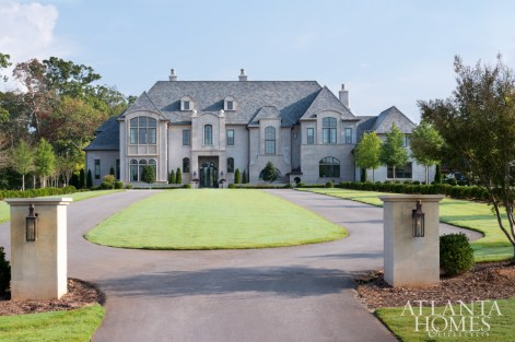 A long oval driveway beckons guests inside, while a stucco and stone exterior nod to the architecture's French traditional style.