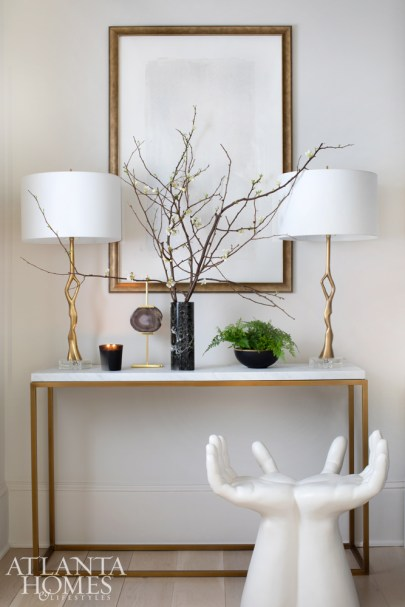 A gallery hallway is a study in brass, marble and white with a console from Restoration Hardware, lamps from Williams Sonoma Home, art from Dixon Rye and the hands stool from Global Views.