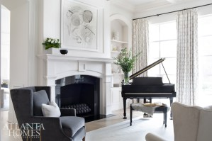 Chairs upholstered in Kravet velvet and the existing piano provide contrast against the white walls and art from B.D. Jeffries. The glass-top side table is from Townhouse by Robert Brown.