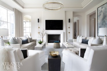 Amtower transformed the family room, removing a massive, stacked-stone fireplace as well as heavy moldings from the archways. Custom waterfall tables with white concrete tops from Grey and a glass- and-brass chandelier from Williams Sonoma Home add lightness, as do sofas by Dmitriy & Co. and pillow fabrics through R Hughes.