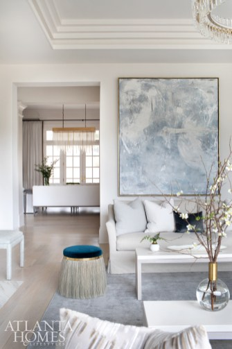 A commissioned painting by Hutton Snellings echoes the palette shift to soft blues and creamy whites. The room is accented by rich fabrics, as in the velvet pillows from Peridot West and a stool fringed with horsehair by Konekt with Holland & Sherry velvet through R Hughes.