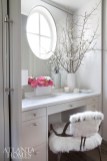 A makeup vanity area with custom cabinetry can be closed off behind pocket doors.