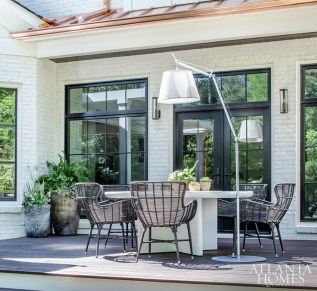 On a dining patio located outside the kitchen, a large lamp by Artemide shines light on a table by Kettal and chairs by Palecek.