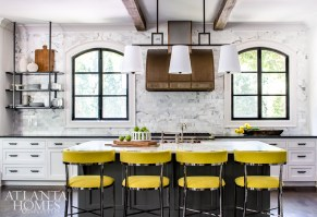 A set of stools covered in a bold chartreuse fabric from Vanguard Furniture pop against the dark gray island in the newly refreshed kitchen. The custom pendant is from Lowcountry Originals.