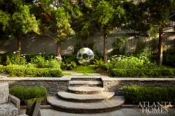 A complete landscape overhaul by Howard Design Studio saw the addition of retaining walls to create a multilevel backyard. The walls are stacked Cherokee Stone—a locally quarried material often used in Buckhead gardens during the 1920s—and are lined with fragrant rosemary clipped to resemble hedges. Howard also added features such as a koi pond and stainless steel garden sculpture by British artist David Harber. The teak furniture is from Sutherland.