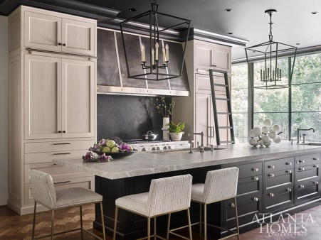 Bleached cherry perimeter cabinetry and a black-painted island from Downsview Kitchens by Design Galleria Kitchen and Bath Studio reference the simple palette used throughout the interior.