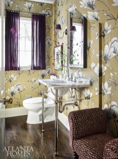 The bold, but airy patterned Harlequin wallpaper refrains from overwhelming the powder room.