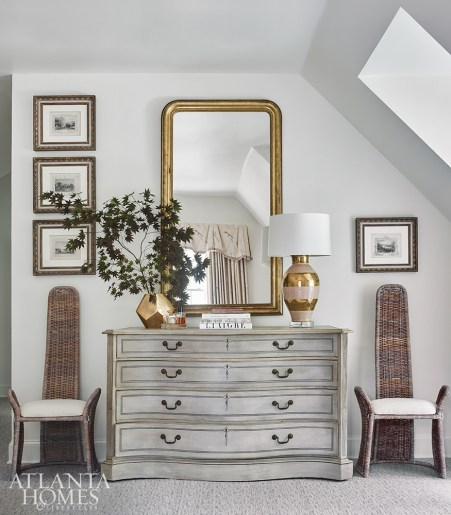 right To contrast the master suite's ladylike design, a quirky pair of vintage chairs from Interiors Market flanks a gray antique chest. Burgess balanced the room's sloping rooflines with a creative arrangement of the client's art collection.