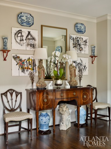 The breakfast room features a blend of styles and ages, including antique furniture and abstract art that is attributed to the late Atlanta decorator, Jay Young. Edgar-Reeves reworked a pair of wooden figures into lamps atop the sideboard.
