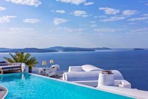 The pool deck at the Katikies Santorini overlooks the island's caldera below.