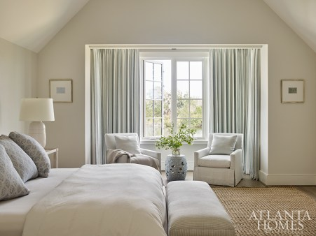 """""""I don't like to compete with the outdoors,"""" says Webb, who kept the guest bedroom's drapery soft and simple. A Ralph Lauren linen adorns the bed pillows, while a bench from Serena & Lily sits at the end of the bed."""