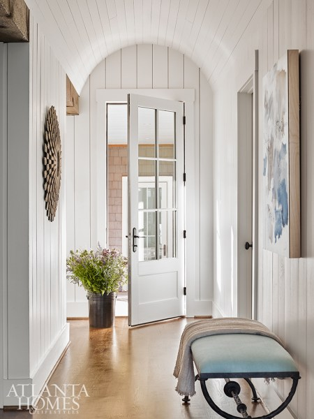 An arched ceiling distinguishes the side entrance, where contemporary artwork and a wood sunburst mirror echo the color palette used throughout the interior.