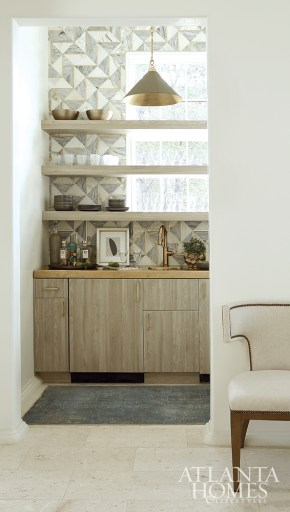 The designers created a splash with a distinctive marble and brass tile backsplash in the butler's pantry.
