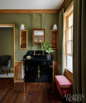 A handsome space for his bath and dressing room features Holland & Sherry tweed upholstery on the walls and pecky cypress trim sourced near the family's farm in South Georgia. The custom brass washstand features black marble and unlacquered brass, and industrial-style exposed plumbing inspired by a similar example found in New York.