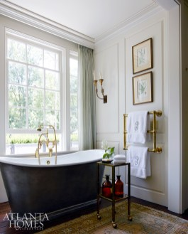 Overlooking the garden is a St. Bordeaux soaking tub by The Bath Works, Inc.