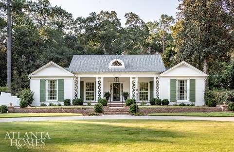 """""""This house looks like no other on the street. You can't help but get a smile on your face when you see it,"""" says architect Brandon Ingram of the facade he conceptualized as a garden cottage in the city. The shutters, painted in Farrow & Ball Calke Green, give the exterior a verdant look, as do the trellis-inset columns."""