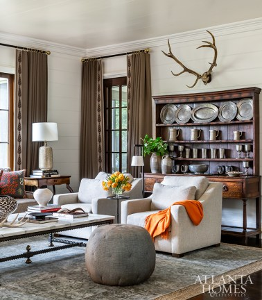 """With a mix of antiques and fresh finds on display, the family room serves as a quiet nod to designer Dan Carithers, who was both a friend and former mentor to Bromenschenkel (she worked for him in the late 1990s). """"He used a lot of brown and white,"""" she says. """"In fact, the antlers on our wall used to hang in his long room, so this space is almost like a wink to Dan."""""""