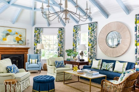 The original beamed ceilings were painted to lighten the space, while a mix of bold colors add vibrancy. Citrus hues mix with hints of ocean blues in the Schumacher drapery fabric that frames the great room.