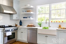 White subway tiles, open shelves and a large farmhouse sink create an authentic environment.