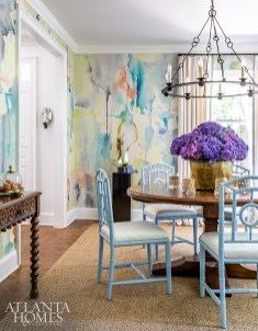 Watercolor-inspired wallpaper by Phillip Jeffries envelops the whimsical dining room that features a pedestal dining table with painted bamboo chairs.