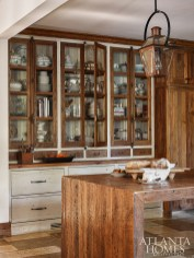 A peek into the pantry offers a glimpse of the couple's heirloom serveware that has been passed down through generations, which is also displayed in glass-front cabinetry.