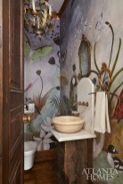 A fanciful mural-style wallpaper from Anthropologie adds panache to the petite powder room.