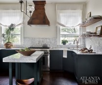 Thick marble countertops complement the deep green cabinetry and bronze hood in the recently renovated kitchen.