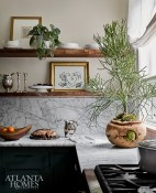 Wood shelving with a live edge adds a sense of rusticity to the more tailored finishes in the bright and airy kitchen.