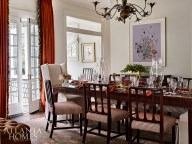 Custom wing chairs balance the antique table and chairs from Parc Monceau in the formal dining room. The antique brass floral chandelier is Maison Jansen through Foxglove Antiques & Galleries.