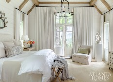 Designed with serenity in mind, the master bedroom features white walls and furnishings, including an upholstered headboard and a plush chair, both covered in fabric from Cowtan & Tout. The iron rope chandelier is by Paul Ferrante through Ainsworth-Noah.