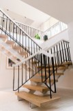 Stripped of its dated carpeting and beautifully refinished, the entire home centers around this one-of-a-kind floating staircase.