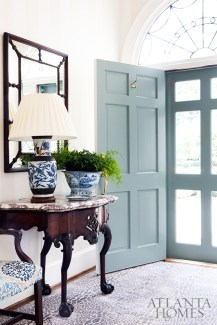 The slate blue door opens to reveal an antique English Regency console with blue-and-white porcelains. Combined with blue leopard carpet by Stark, it's a decidedly dramatic entrance.