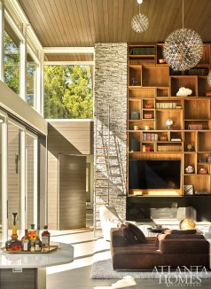 """The built-in walnut cabinetry, a stylish way to showcase pieces from the owners' collection, adds a warm contrast to the cultured stone walls. """"We thought it was important to bring the wood into the mix to get that warmth,"""" says designer Melanie Millner. """"That was a key factor in making the space work."""""""