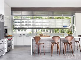 The reflective, flat-front cabinetry by Poggenpohl grounds the kitchen, which features a cypress ceiling and porcelain tile flooring. Suspended from the ceiling, a large cabinet with frosted glass on both sides creates storage without interfering with the natural light from the bay window. The stools are from Design Within Reach.