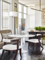 A dining bench and hide-covered chairs surround a white tulip table by Saarinen from Knoll in the dining area. The floor lamp is from CB2.