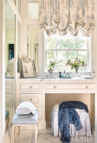 The wife's vanity area feels light, airy and beautiful. On the dressing table are some antique silver pieces, part of the client's personal collection. The bench is upholstered in Brunschwig & Fils' Creek Figured Woven Fabric.