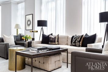 A rug unifies three distinct areas in the living room, which provides room for dining, conversation and work. The tripod lamps are from Townhouse by Robert Brown.