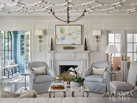 Just off the entry, the formal living room sets the tone for the rest of the house, featuring intriguing architecture detail, including a ceiling molding sourced from The Fischer & Jirouch Company and made from 100-year-old molds to create an authentic vintage effect. The pair of marble coffee tables are the homeowners' family heirlooms. The artwork above the fireplace was commissioned for the space from Atlanta artist Paige Kalena Follmann.
