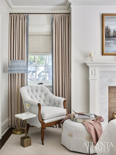 A Wesley Hall Richmond Chair upholstered in Larsen's Axis Blue fabric anchors a corner in the master bedroom. The artwork above the fireplace is by Madison, Georgia, artist Elaine Jackson.