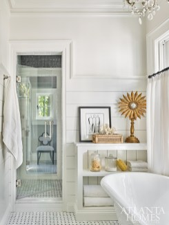 The master bath is divided into his-and-hers spaces, which connect via a double-entry shower. Her space features a spacious soaking tub and ink-on-paper artwork by Atlanta artist Paige Kalena Follmann.
